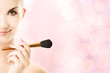 Lovely young woman with a make-up brush Stock Photo - 3714123