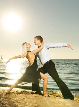 Beautiful young couple dancing tango on the beach at sunset Stock Photo - 3714177