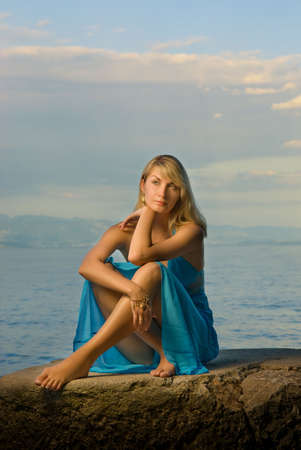 Beautiful young woman relaxing near the sea photo