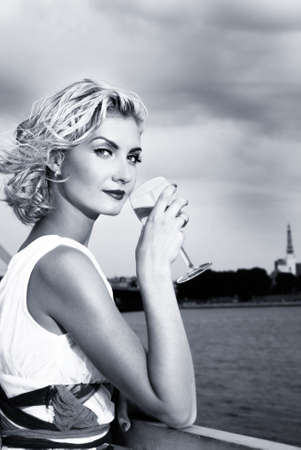 divas: Beautiful blond girl drinks champagne near the river