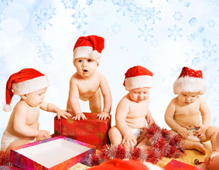 Group of adorable toddlers in Christmas hats packing presents photo