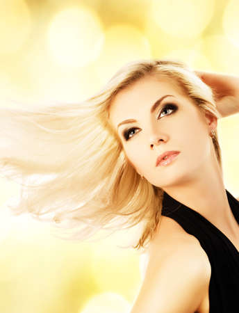 flapping: Beautiful blond woman over abstract golden background
