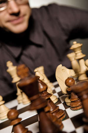 Chess master thinking before making a move (shallow Dof, focus on chess piece) photo