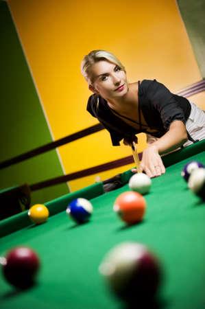 Beautiful blond woman playing billiards photo