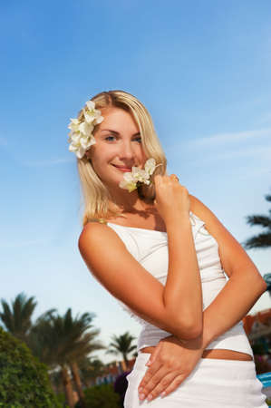 beach blond hair: Beautiful young woman with white flowers outdoors Stock Photo