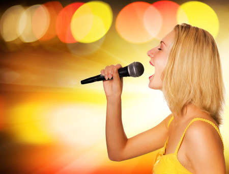 Beautiful young singer on abstract background photo