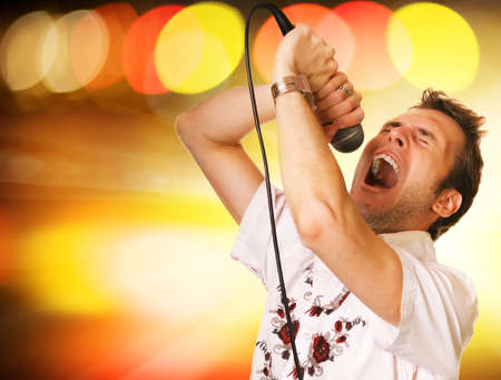 Young guy with a microphone over abstract background photo