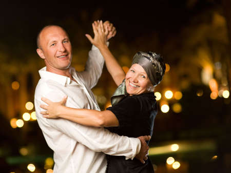 emotional couple: Middle-aged couple dancing waltz at night