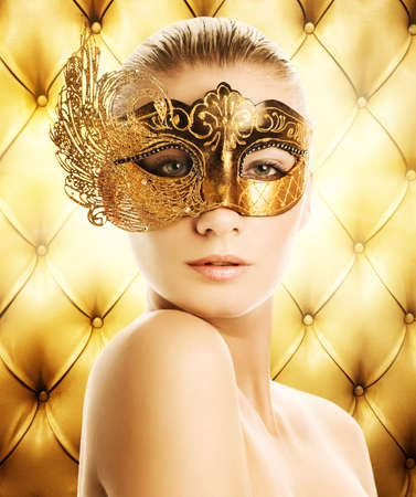 Beautiful woman in carnival mask over abstract background photo