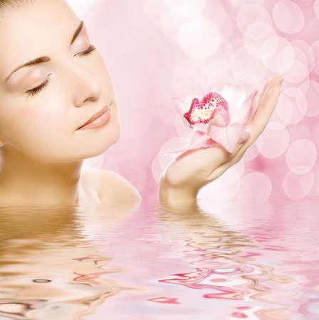 Schöne junge Frau mit Orchidee, die in Wasser