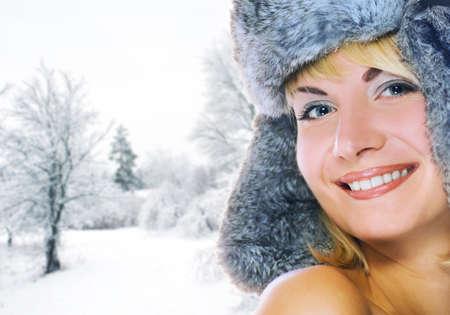 Beautiful young woman in winter fur-cap photo