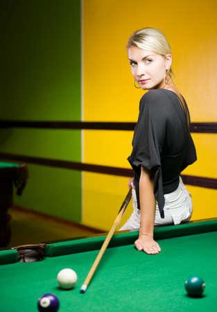 cue sticks: Beautiful blond woman playing billiards Stock Photo