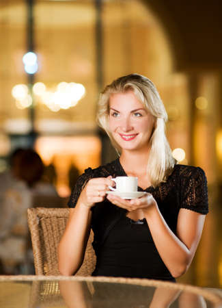Beautiful young woman drinking coffee in a restaurant photo