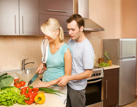 Young couple making vegetable salad in the kitchen photo