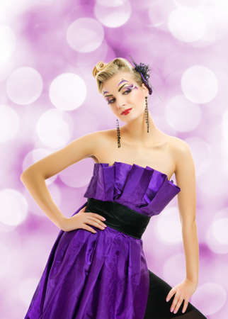 Beautiful woman in purple dress over abstact blurred background photo