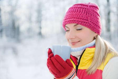 Beautiful blond woman drinking hot tea outdoors photo