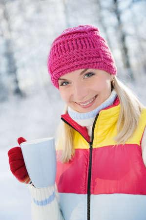 Beautiful blond woman drinking hot tea outdoors Stock Photo - 4101917