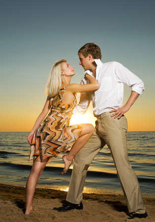 Young couple in love near the ocean at sunset Stock Photo