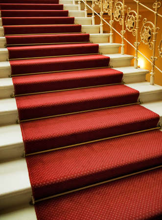 Stairs covered with red carpet photo