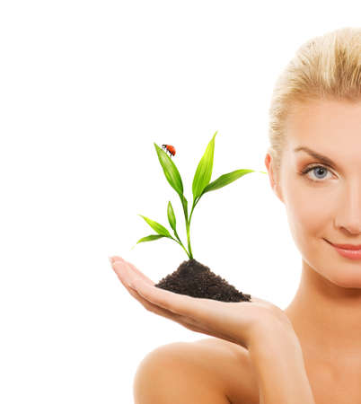 Beautiful blond woman holding young plant photo