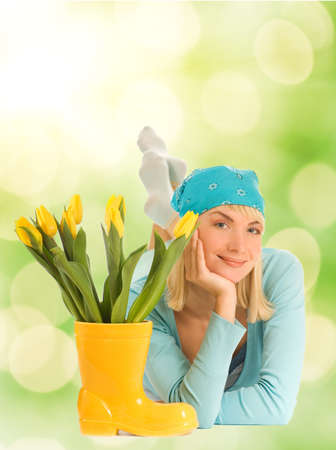 Beautiful teenager with spring flowers over abstract blurred background photo