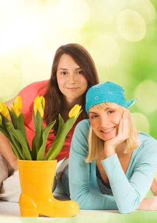 Beautiful teenagers with spring flowers over abstract blurred background photo
