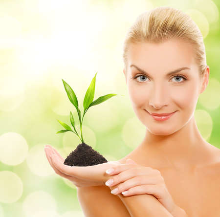 young plant: Beautiful blond woman with young plant over abstract blurred background Stock Photo