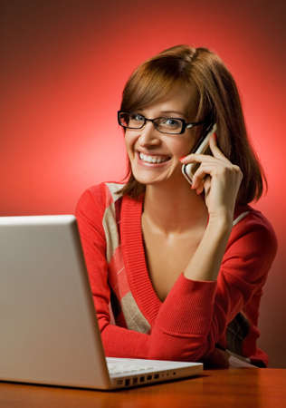 Beautiful smiling woman working on her laptop and talking on cell phone Stock Photo - 4129983