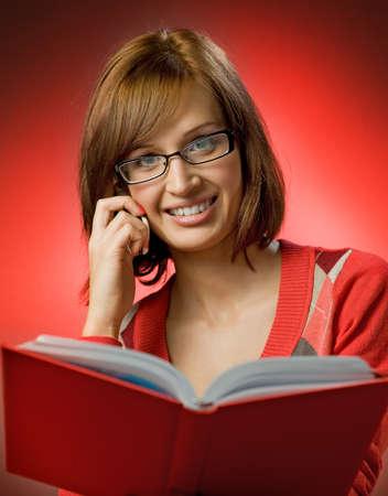 directorio telefonico: Hermosa mujer pelirroja buscando un n�mero de tel�fono en la gu�a telef�nica Foto de archivo