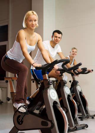 haciendo ejercicio: Grupo de personas haciendo ejercicio en una bicicleta en un gimnasio Foto de archivo