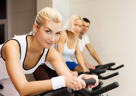 Group of people doing exercise on a bike in a gym Stock Photo - 4143414