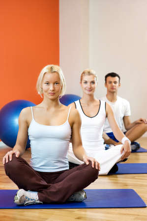 pilates man: Group of people doing yoga exercise Stock Photo