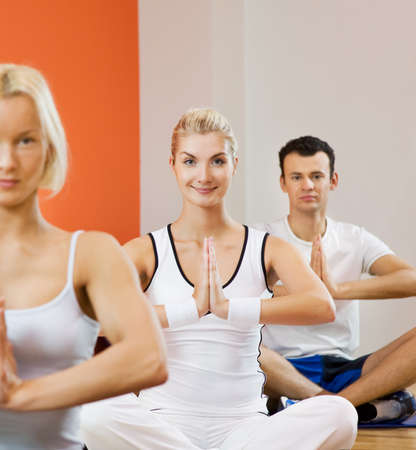 Group of people doing yoga exercise (focus on a woman in the middle) Stock Photo - 4143412