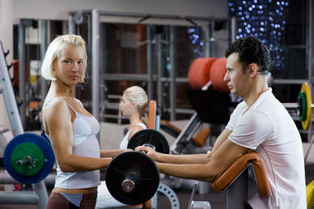 Handsome young man lifting weights assisted by a female trainer Stock Photo - 4143405