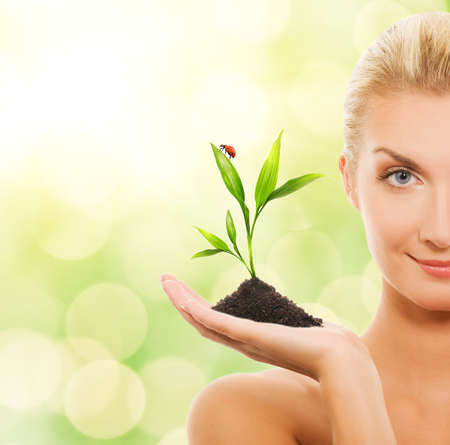 Beautiful blond woman with young plant over abstract blurred background Stock Photo
