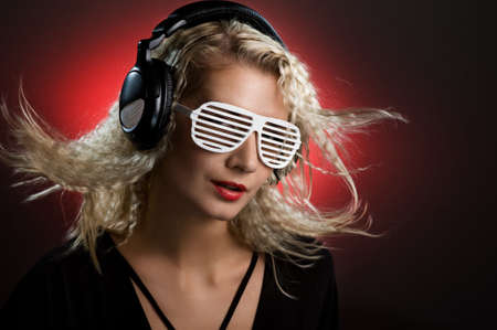 Stylish blond woman with shutter glasses and headphones photo
