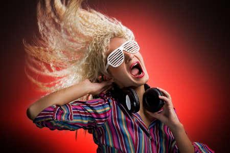 gente loca: Bella mujer bailando con auriculares y gritando Foto de archivo
