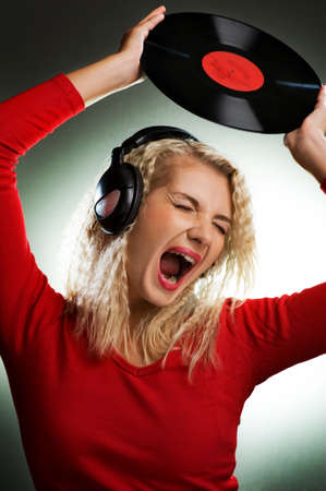 Singing beautiful woman with headphones and vinyl record