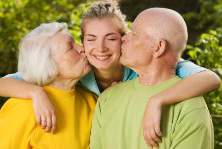 Grandparents kissing their granddaughter Stock Photo