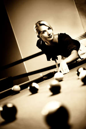 cue sticks: Beautiful blond woman playing billiards (toned in sepia) Stock Photo