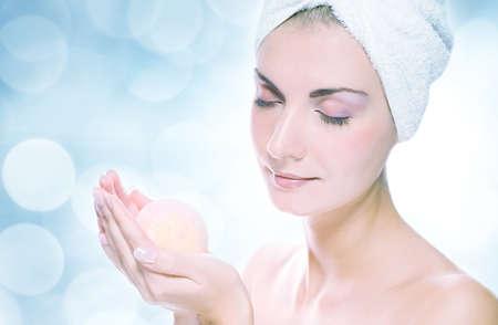 bomba a orologeria: Giovane e bella donna con bagno aromatico palla oltre astratto sfondo sfocato Archivio Fotografico