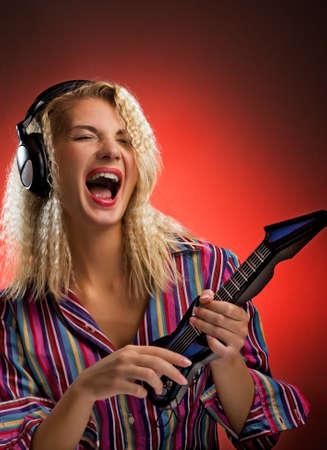 electro: Sch�ne junge Frau mit Kopfh�rer spielen kleine Elektro-Gitarre Lizenzfreie Bilder