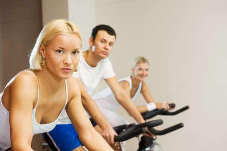 Grupo de personas haciendo ejercicio en una bicicleta en un gimnasio Foto de archivo - 4206125