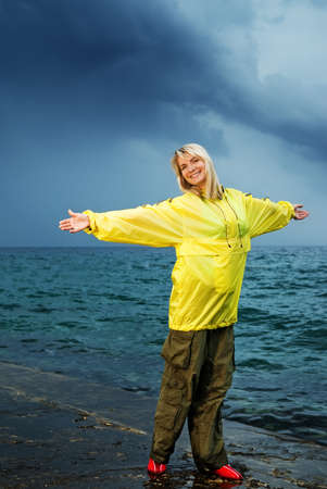 Young woman in yellow raincoat near the ocean at storm photo