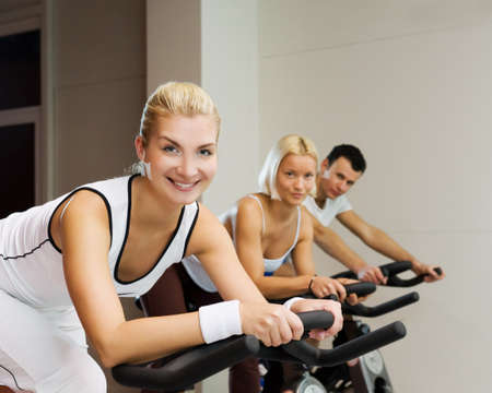 Group of people doing exercise on a bike in a gym photo