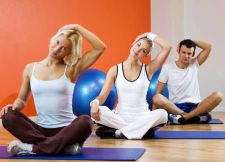 Group of people doing yoga exercise (focus on woman in the middle) Stock Photo - 4250548