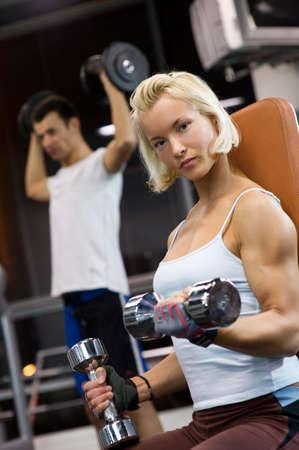 Strong beautiful woman lifting heavy dumbbells photo