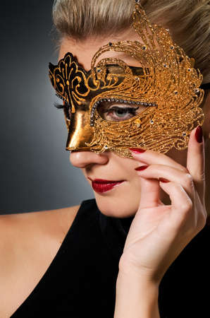 Lovely young woman with carnival mask on her face photo