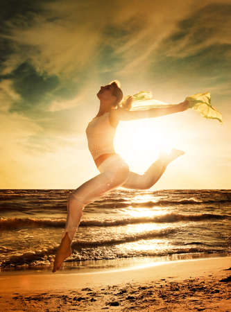 Beautiful young woman jumping on a beach at sunset photo