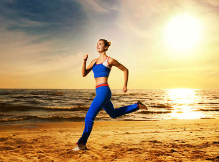 Beautiful young woman running on a beach at sunset Stock Photo